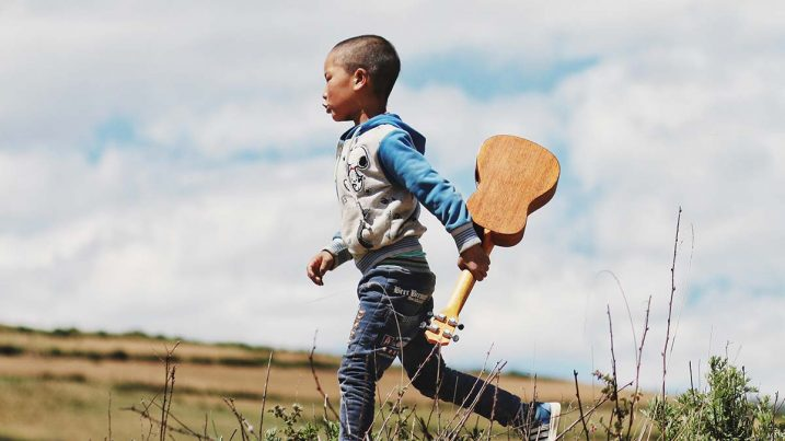 child running with guitar